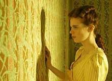 Girl staring at yellow wallpaper